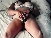 Suntanned milf rubbing her clit on her bed